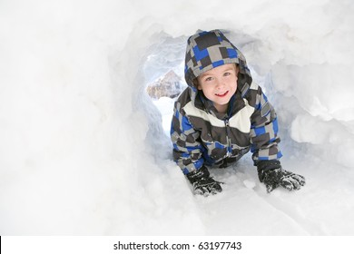 Young boy playing in a snow tunnel