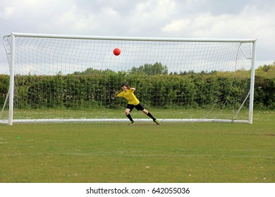 Young boy playing soccer as a goalkeeper preparing to save a goal as a red ball approaches.