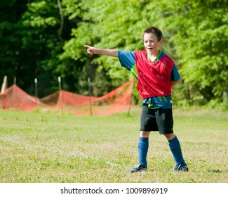 Young Boy Playing Soccer Outdoors in the Spring