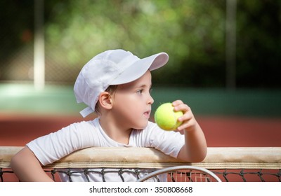 Young boy playing tennis at a clay court