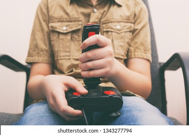 Young boy playing video game with a retro joystick. Gaming joystick from the mid-1980s. Close up.