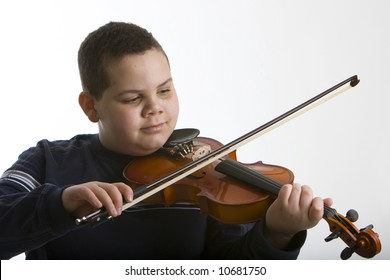 Young boy playing a violin against a light background
