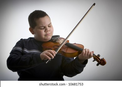 Young boy playing a violin against a light vignetted background