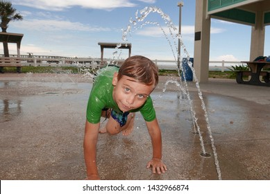 Young boy playing in water fountains at a beach splash pad