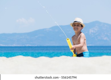 Young boy  playing with water pistol by the sea