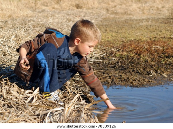 Young boy playing in water of a wetland pond - getting dirty catching frogs and fish