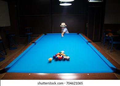 Young boy plays billiards