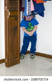 a young boy plays hide and seek by hiding in the closet behind clothing
