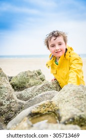 A young boy plays near a rock pool in the UK on a rainy summers day wearing a yellow mackintosh.
