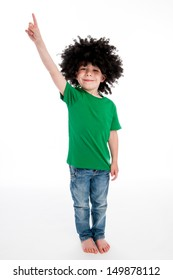 Young boy pointing his finger in studio on white background with a big black funny wig.