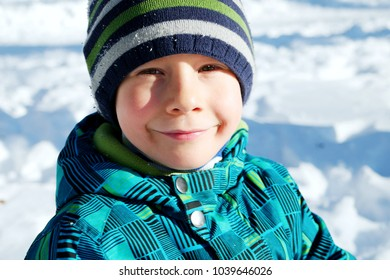 Young boy portrait in sunny winter day. Happy boy looking to the camera. Snow concept