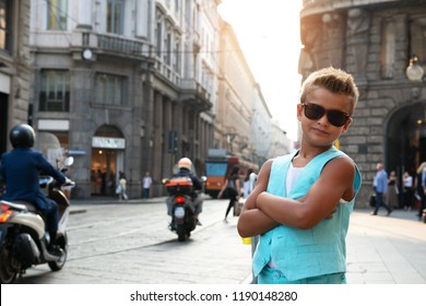 Young boy posing in milanese street with old tram on background. Cute happy 6 years old boy posing in Milan, Italy. Kid's street fashion. Trendy boy in suit walking in the Italian capital of fashion.