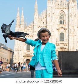 Young boy posing with pigeons in the milanese street with ancient church Duomo di Milano on background. Cute happy 6 years old boy posing in Milan, Italy. Kid's street fashion. Trendy boy in suit