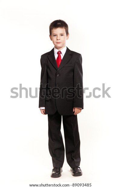 5b28df4a0059 Young boy posing in studio in a black suit and a red tie, business code