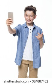 Young boy posing and taking a selfie against a white background.