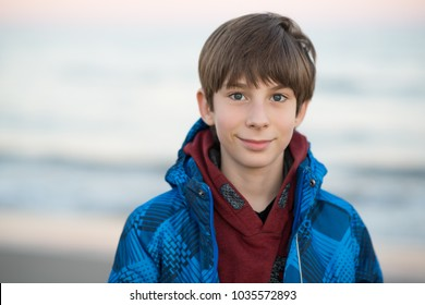 Young boy posing at the winter beach. Cute smiling happy 11 years old boy at seaside, looking at camera. Kid's outdoor portrait.