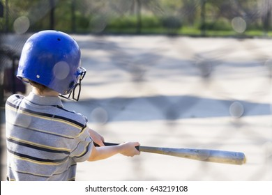 Young boy practicing hitting baseball at the batting cages for the first time, summer scene