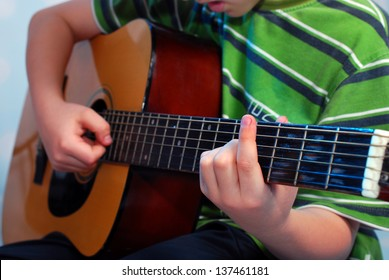 young boy practicing playing the classical guitar