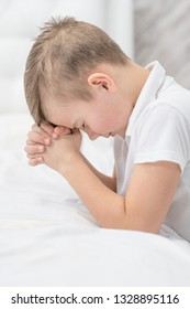 Young boy  praying in bedroom before going to bed
