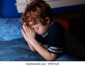 young boy praying at bedtime