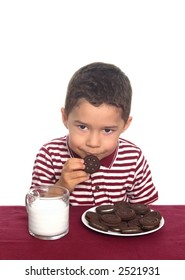 A young boy prepares to eat his cookies and milk