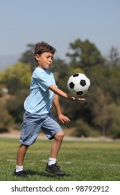 A young boy prepares to kick a soccer ball