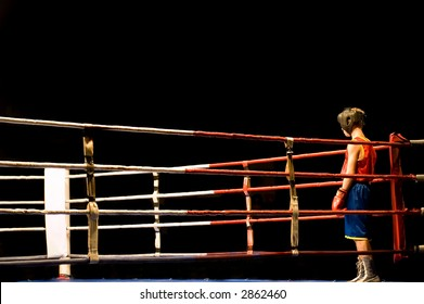 Young boy preparing waiting in a ring for boxing fight