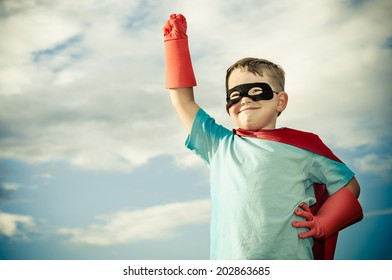 Young boy pretending  to be superhero in vintage filtered image