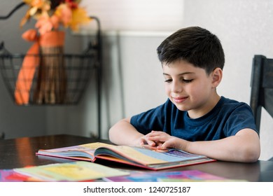 Young boy in the process of reading book around the table