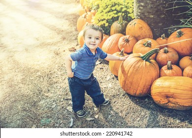 A young boy proudly poses with his hand resting on a pumpkin he has picked out at a farm during the autumn season.  Filtered for a retro, vintage look.