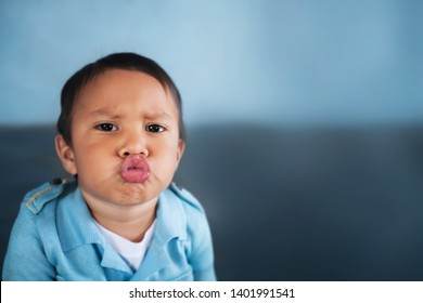 Young boy puckering up his lips to give a kiss and wearing a light blue vintage shirt.