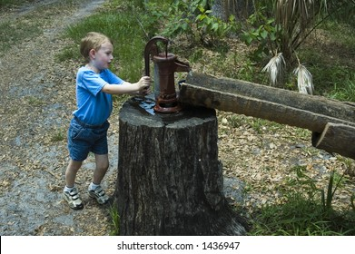 Young boy pumping water from an old hand pump to water trough