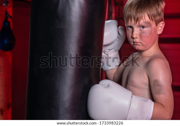 Young boy punching a boxing bag in gym