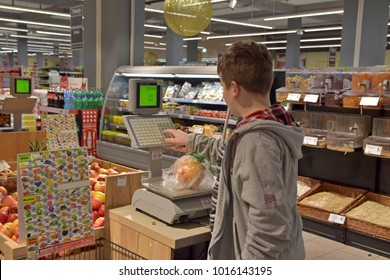Young boy putting fruits on scale in supermarket, Sarajevo, Europe, 02.02.2018