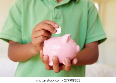 Young boy putting money in piggybank