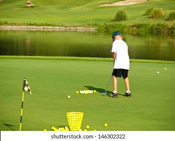 Young boy putting on the green of a golf course.