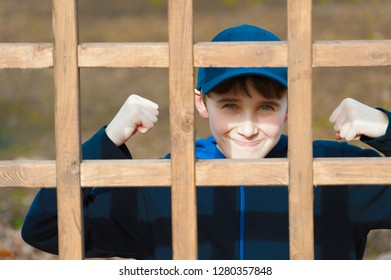 A young boy raises fits with a tight grin while posing for camers behind a wooden latice.