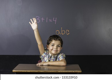 A young boy raising his hand in class.