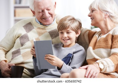 Young boy reading a book with his older grandparents