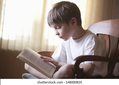 Young boy reading book on chair at home