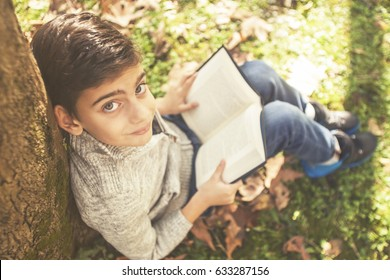 Young boy reading a book outdoors. (Selective focus image toned for vintage effect)