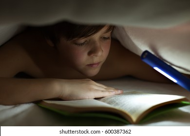 Young boy reading a book under the blanket or quilt - lighting with a flashlight