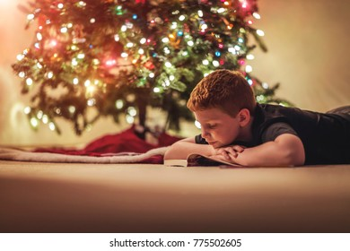 Young boy reading a book under the Christmas tree with added vintage filter and soft focus