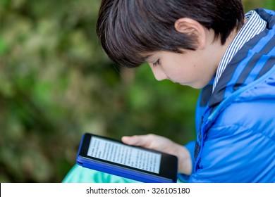 Young boy reading an ebook.