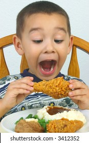 A young boy ready to devour his fried chicken