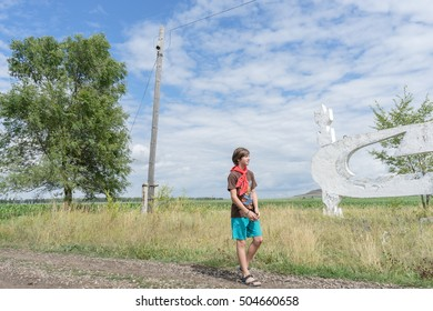 a young boy in a red tie. the boy is in a rural location. boy standing on the road in the field. boy stands near the stele time of the USSR. boy in shorts. red scarf around his neck. pioneer USSR.