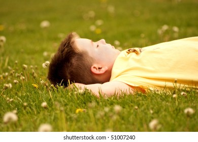 Young Boy Relaxing On Grassy Field