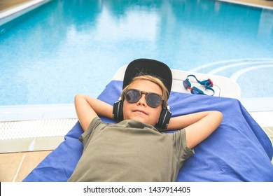 Young boy relaxing outdoor playing music with smartphone Trendy child listen streaming near a swimming pool on a sunny summer day Teen enjoying holidays after end of school resting on a chaise longue