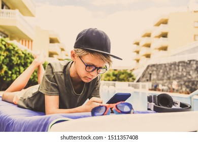 Young boy relaxing outdoor playing with smartphone. Trendy child reads news near the swiming pool on a sunny summer day. Teen enjoying holidays after the end of school. Concept of leisure and freetime