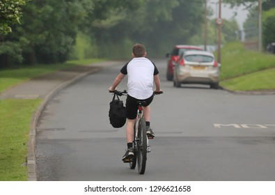 Young boy ride a bike with backpack and without helmet on the road.